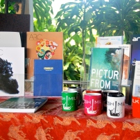The sales table featuring FRESH MILK Mugs, Pictures from Paradise, ARC Magazines and Timed Out by Leon Wainwright