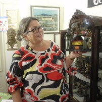 Curator at Landhuis Bloemhof Nicole Henriquez, holding a piece by Maximiliano Nepomuceno