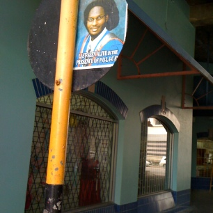 Sign with an I'Akobi poster on the back