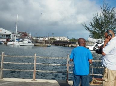 Filmmaker Powys Dewhurst and microbiologist Alvin Cummins on the boardwalk discussing the Bridgetown Dry Dock.